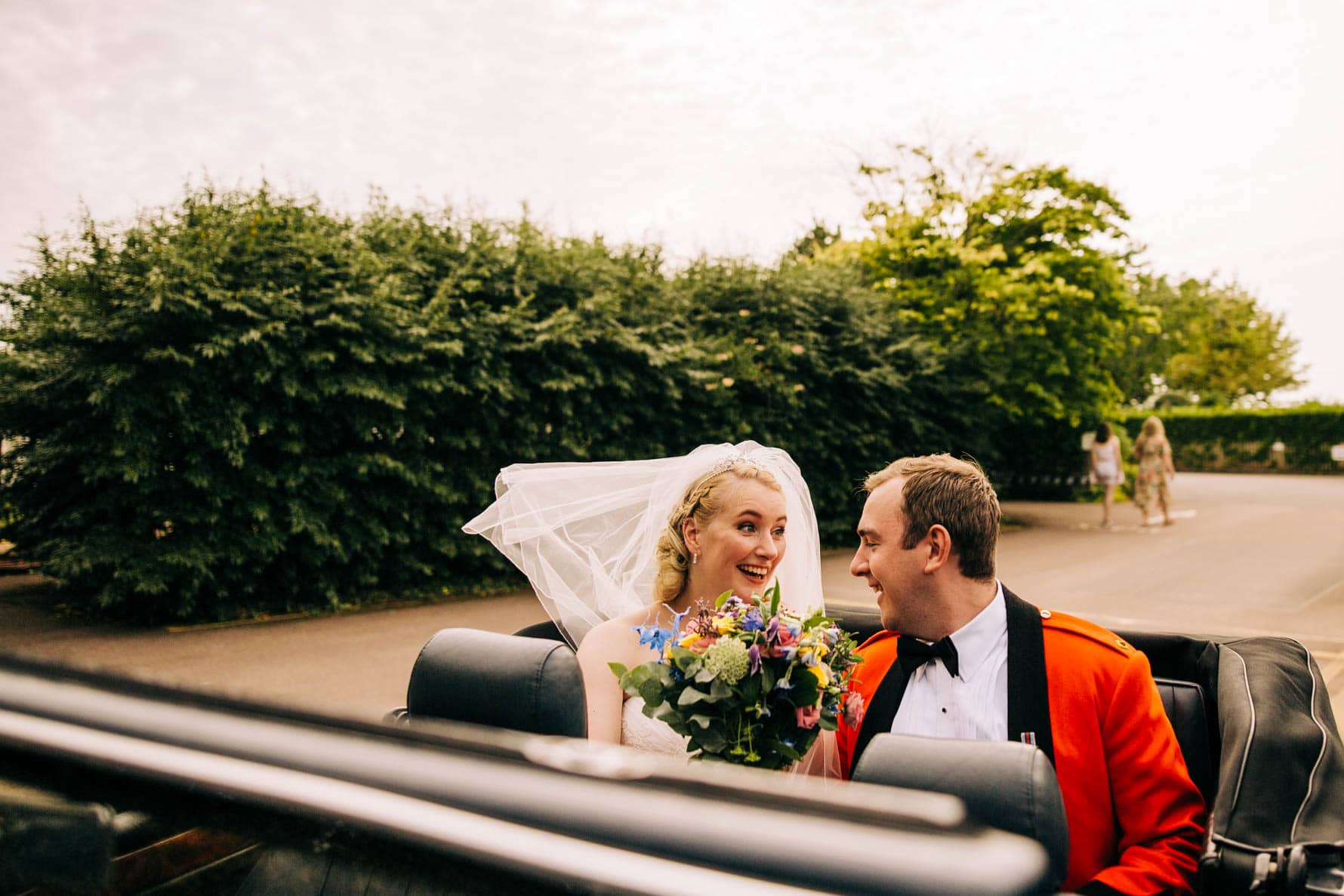 Bride and groom sitting in the back of their wedding car