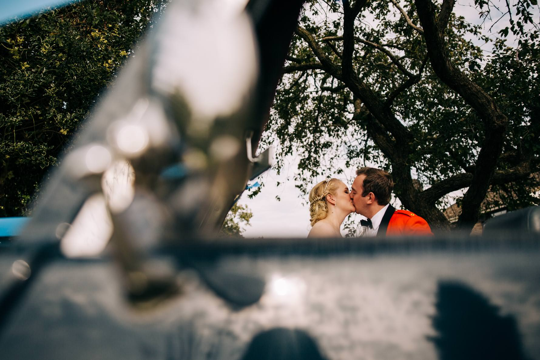 Bride and groom kissing framed by a vintage car