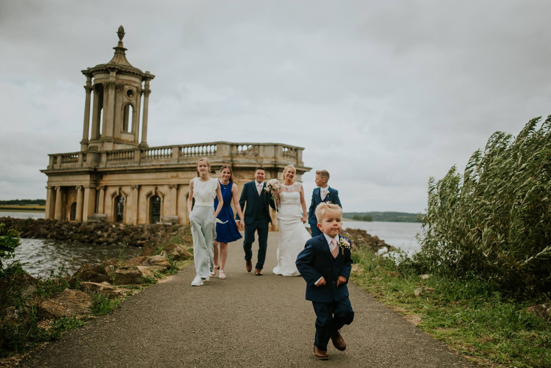 a family walking away from normanton church on their wedding day