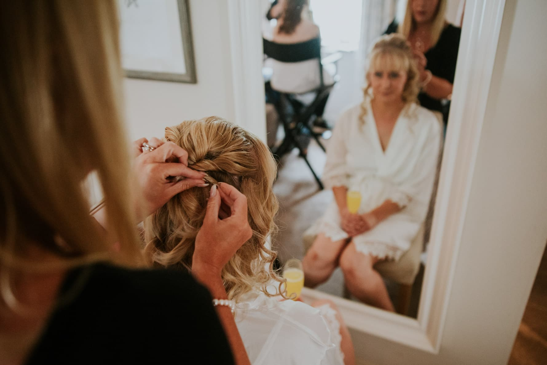 bride having her hair pinned up for her wedding