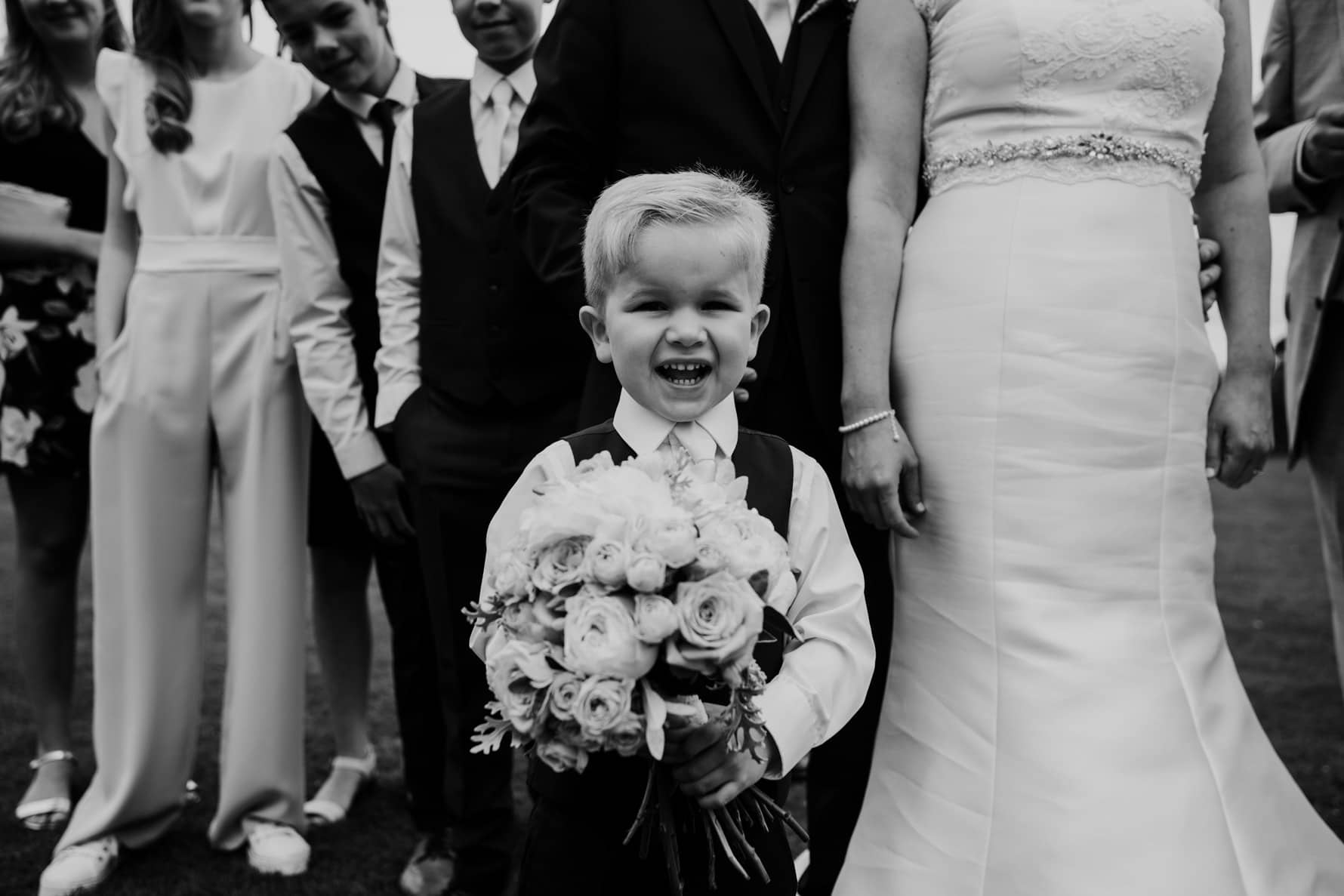 Page boy holding a bunch of flowers in front of the bride