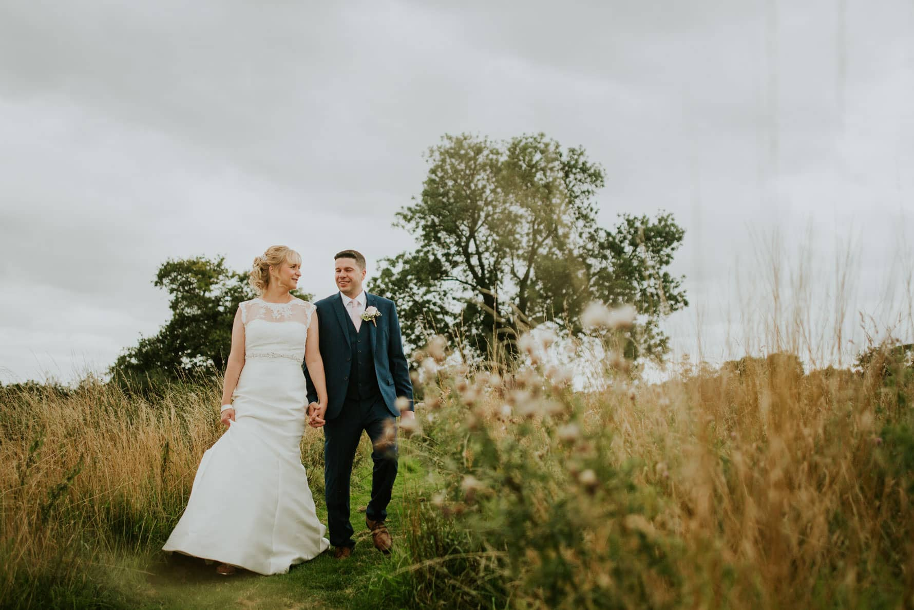 Barnsdale Lodge wedding photographer - bride and groom walking through a wild garden