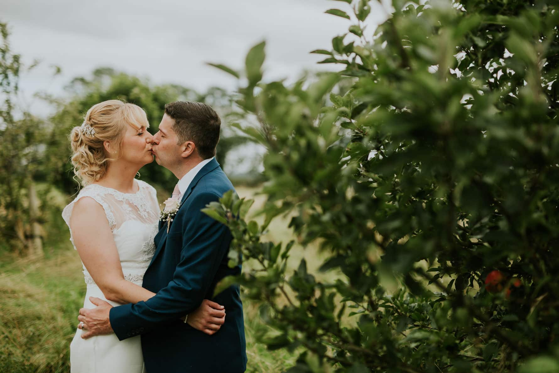 Bride and groom kissing next to an apple tree
