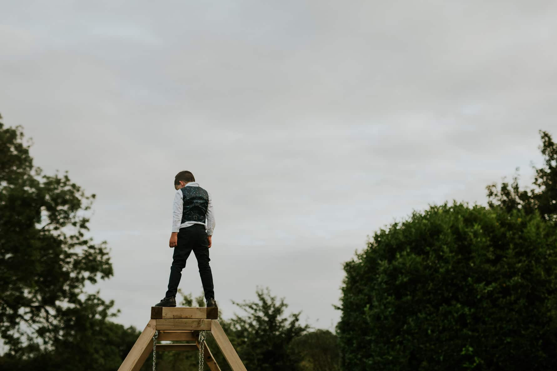 a child standing on the top of a swing at barnsdale lodge