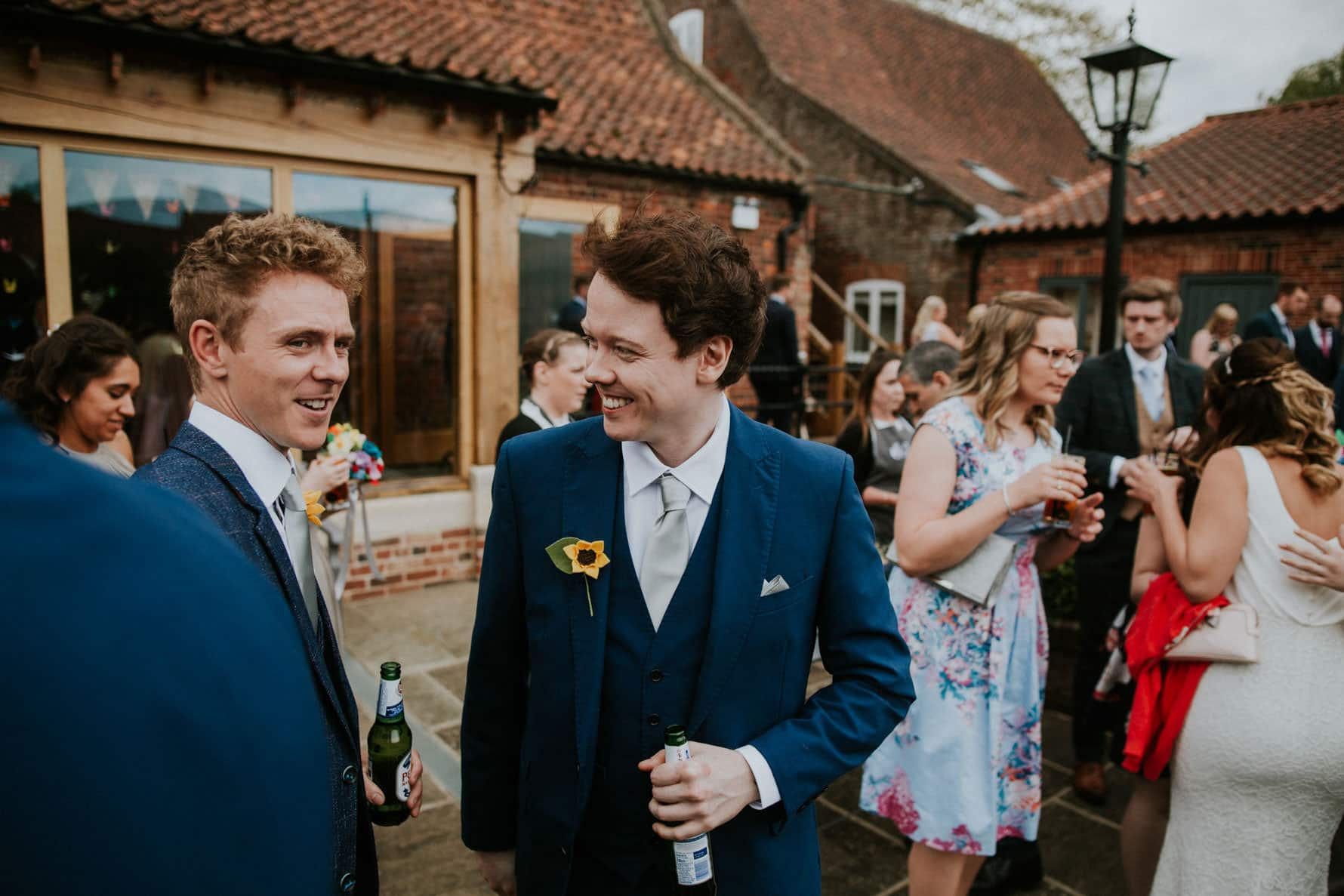 Wedding guests relaxing during the drinks reception at granary wedding barn