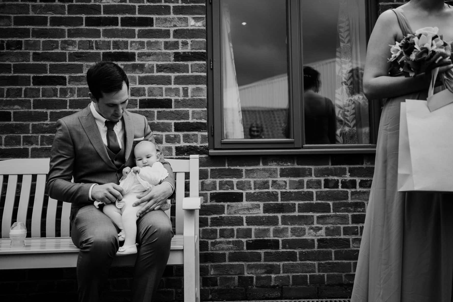 wedding guest sitting with his baby