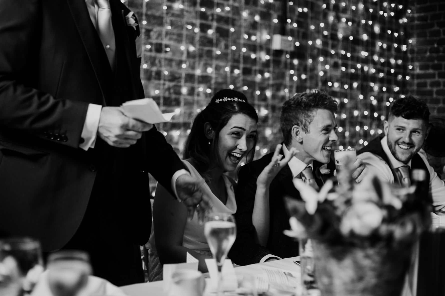 Bride and groom reacting to a wedding speech