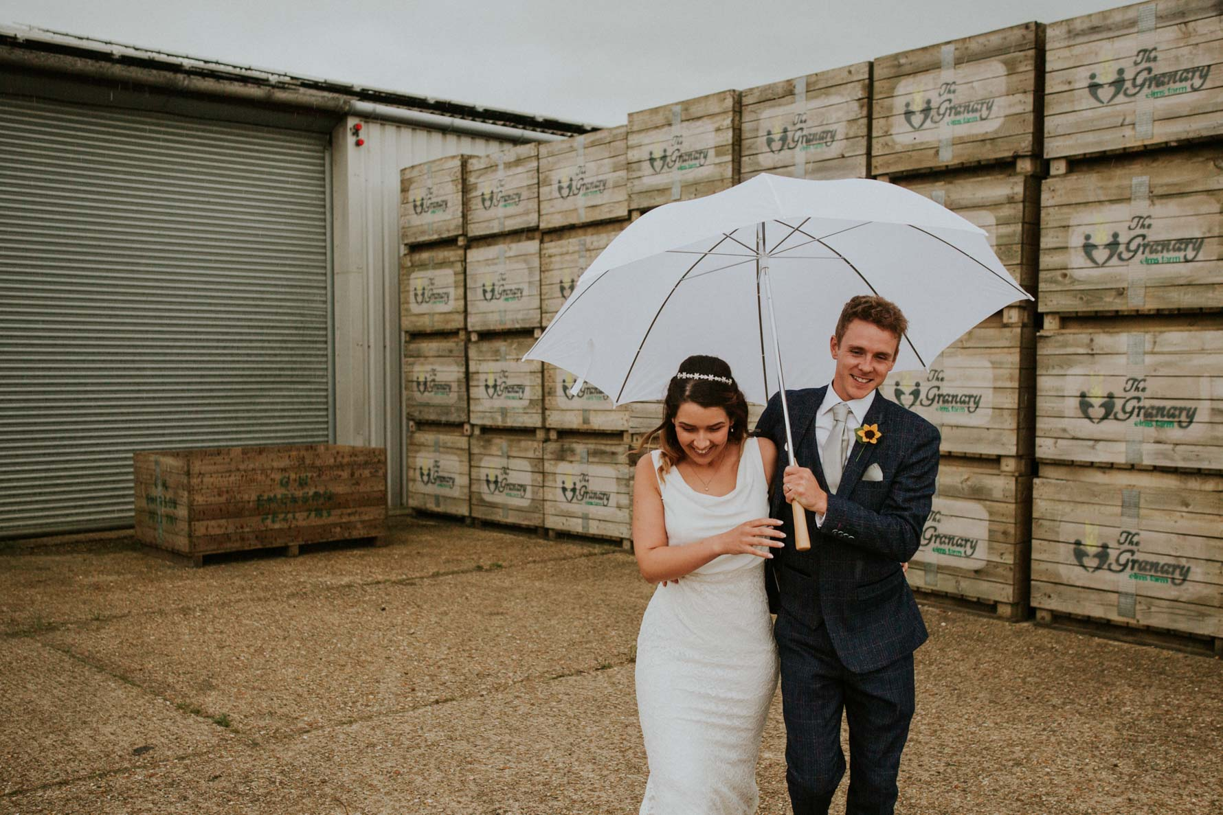 Bride and groom walking and laughing with an umbrella