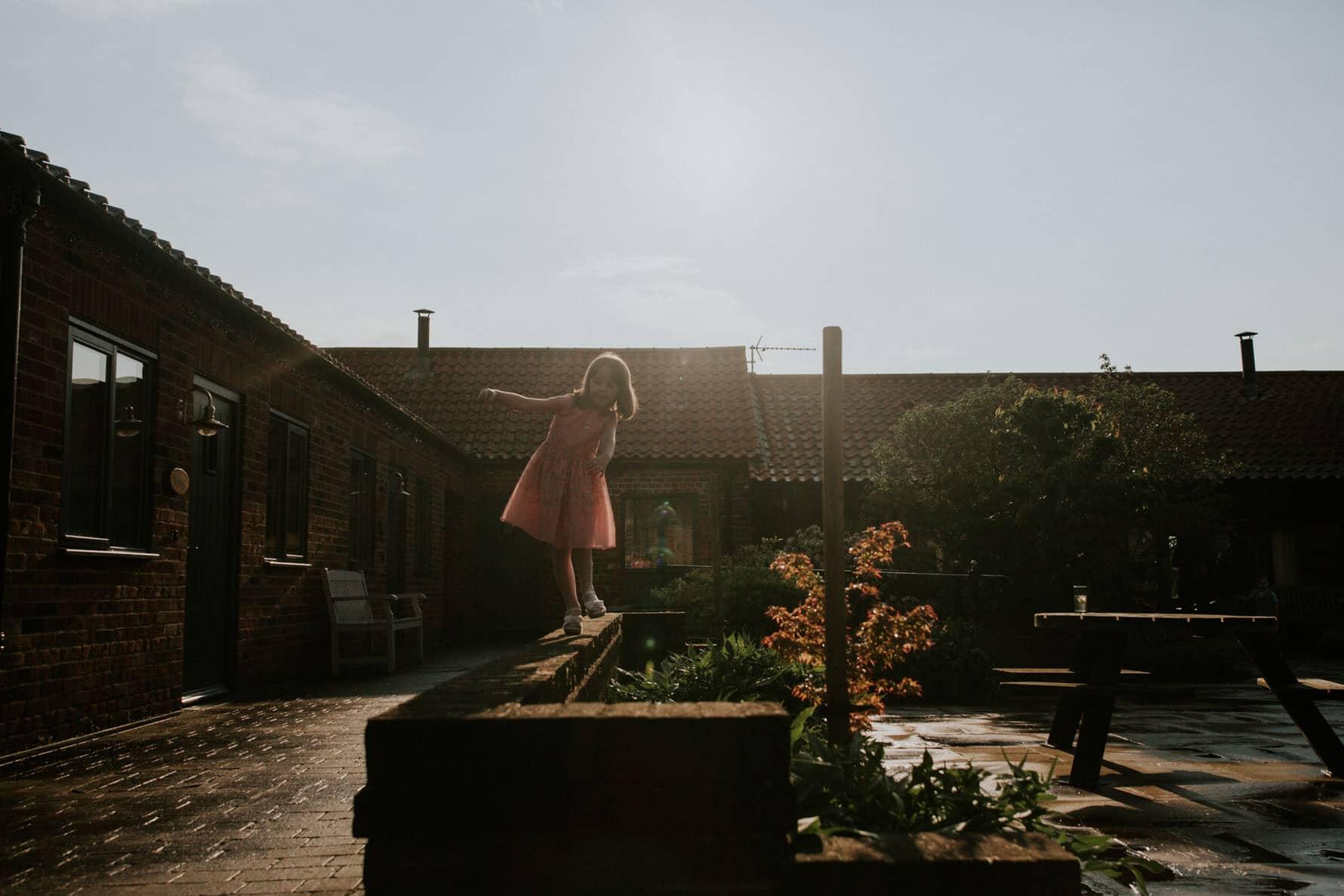 Girl walking along a wall in the granary wedding barn