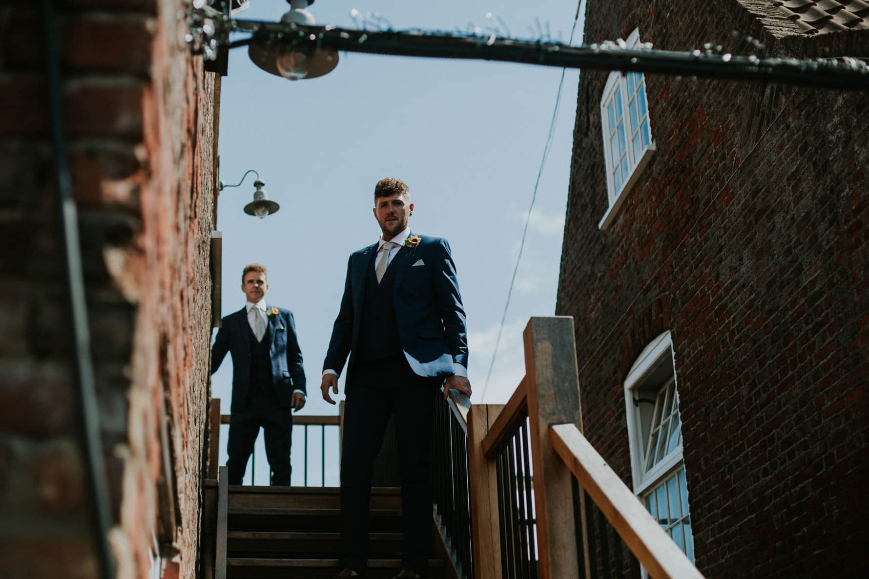 Groom and best man walking down some steps