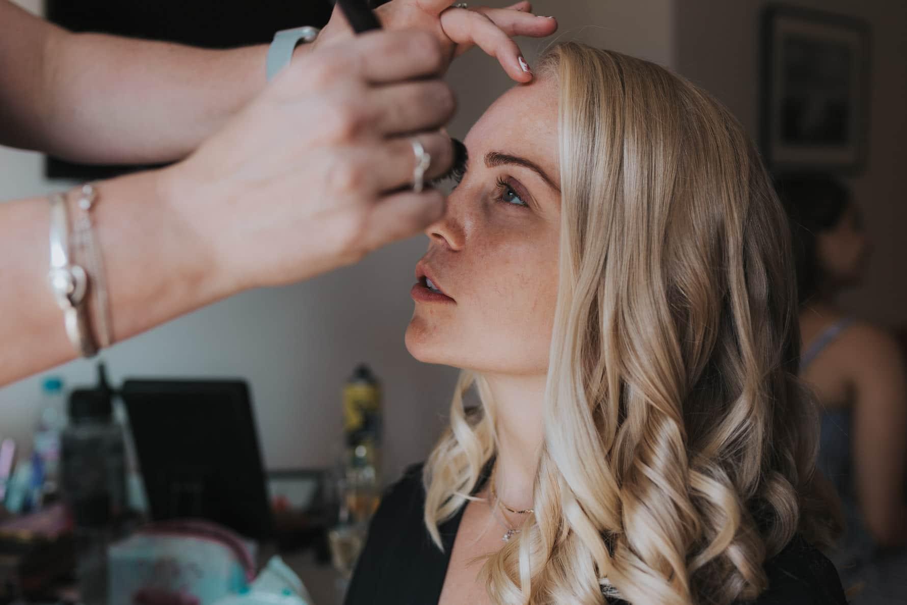Bridesmaid having makeup applied