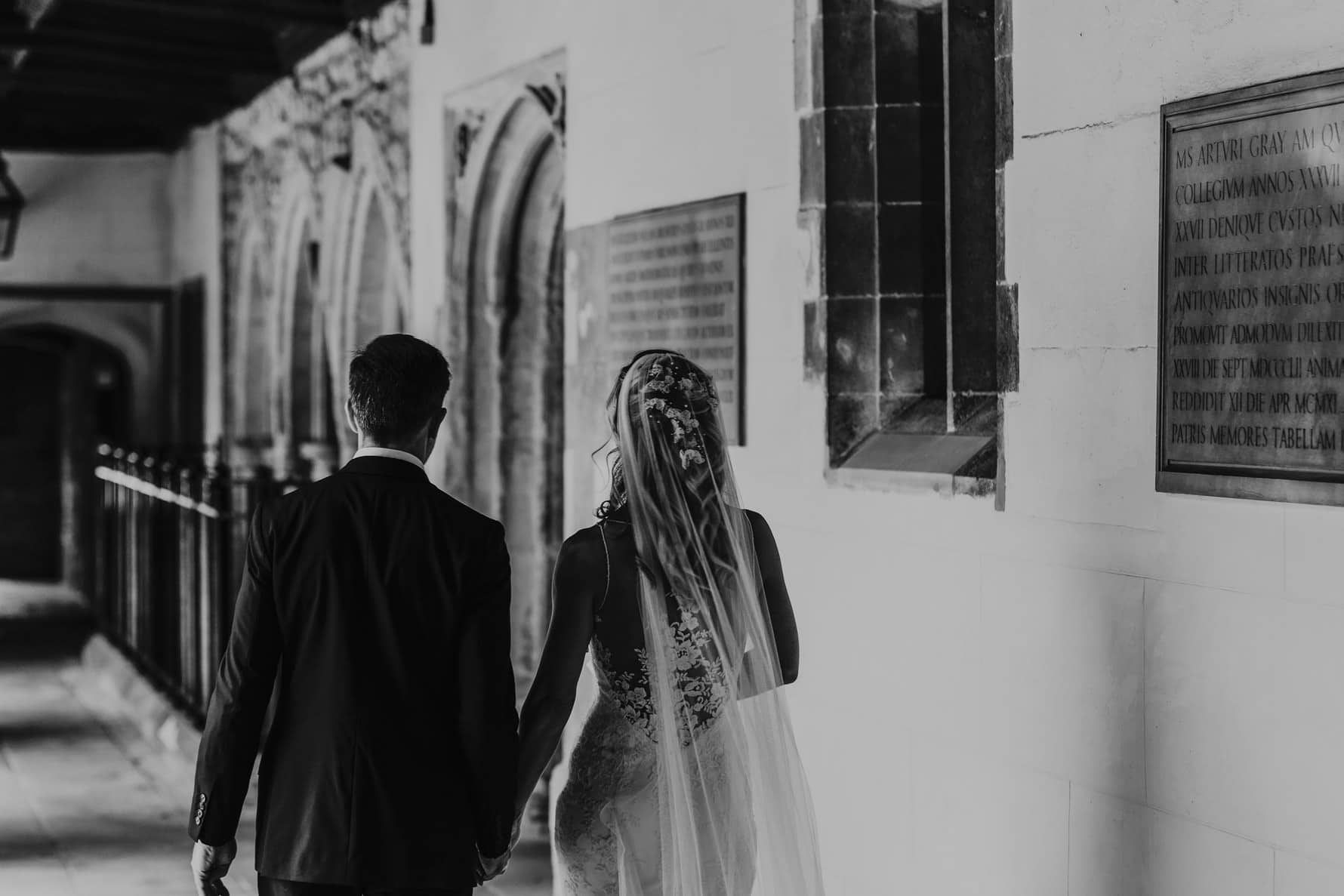Bride and groom walking out of a ceremony at Jesus College