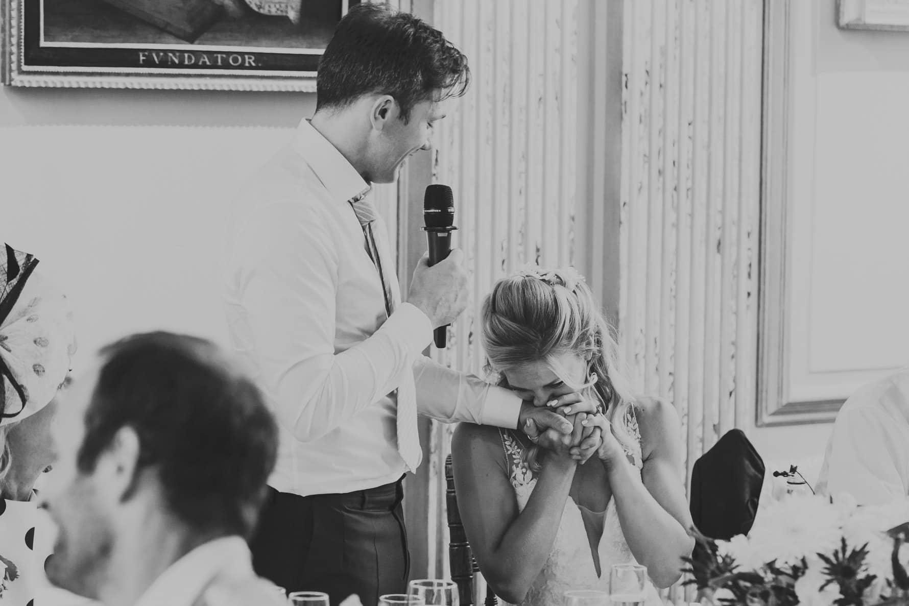 Bride kissing the hand of the groom during wedding speeches