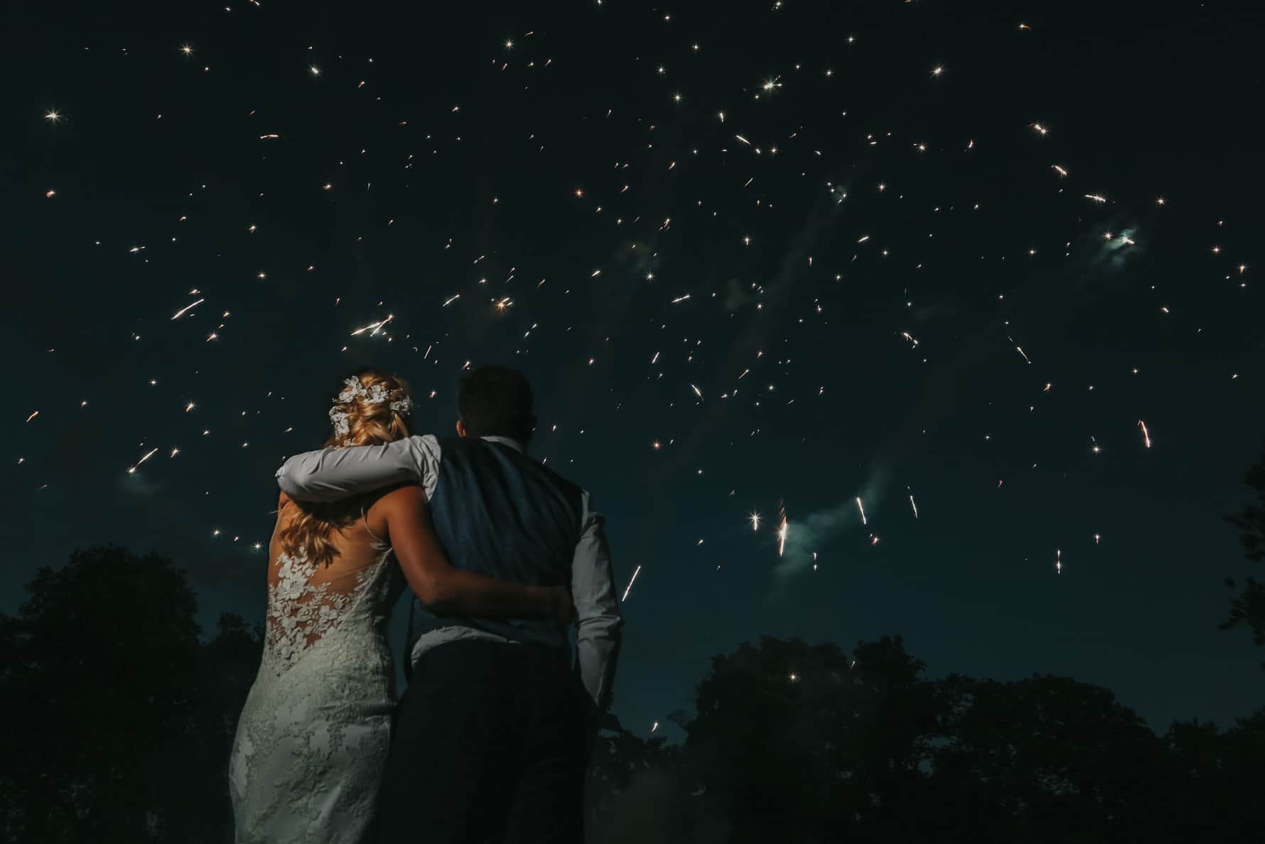 Bride and groom stood in front of fireworks at their Cambridge wedding photographer