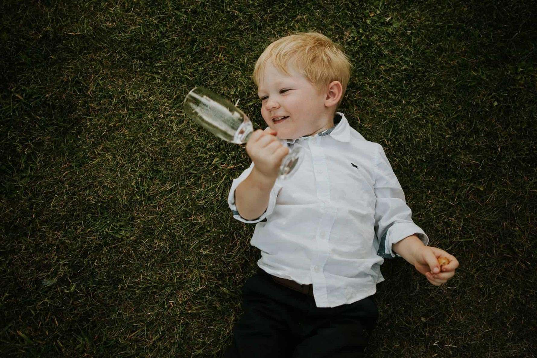 Boy holding a wine glass and laying down