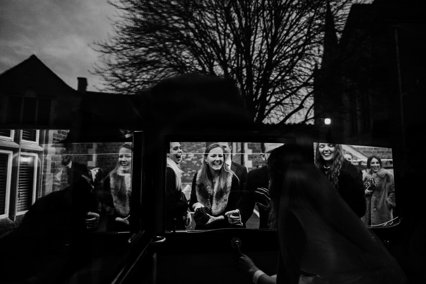 wedding guests celebrating as the bride and groom leave in their car