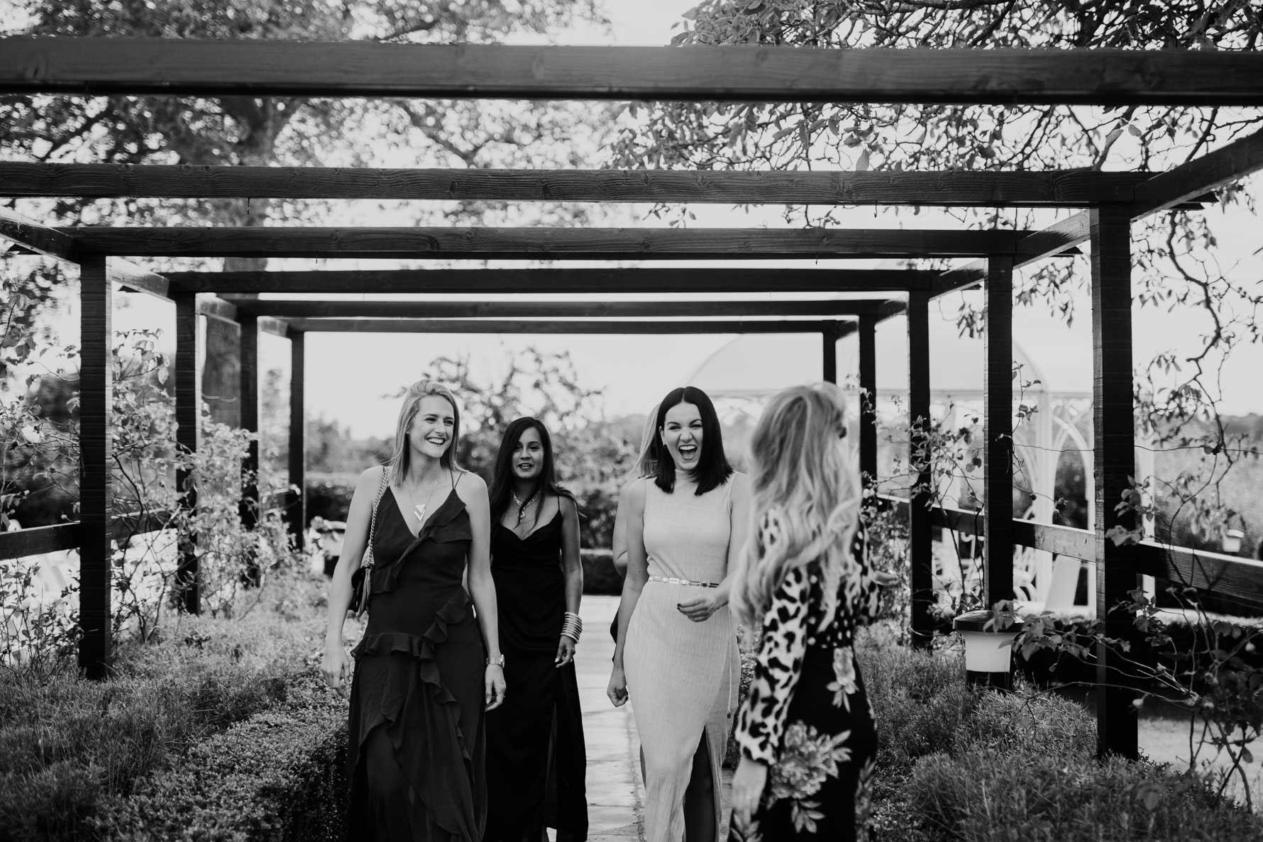 four wedding guests walking through a garden