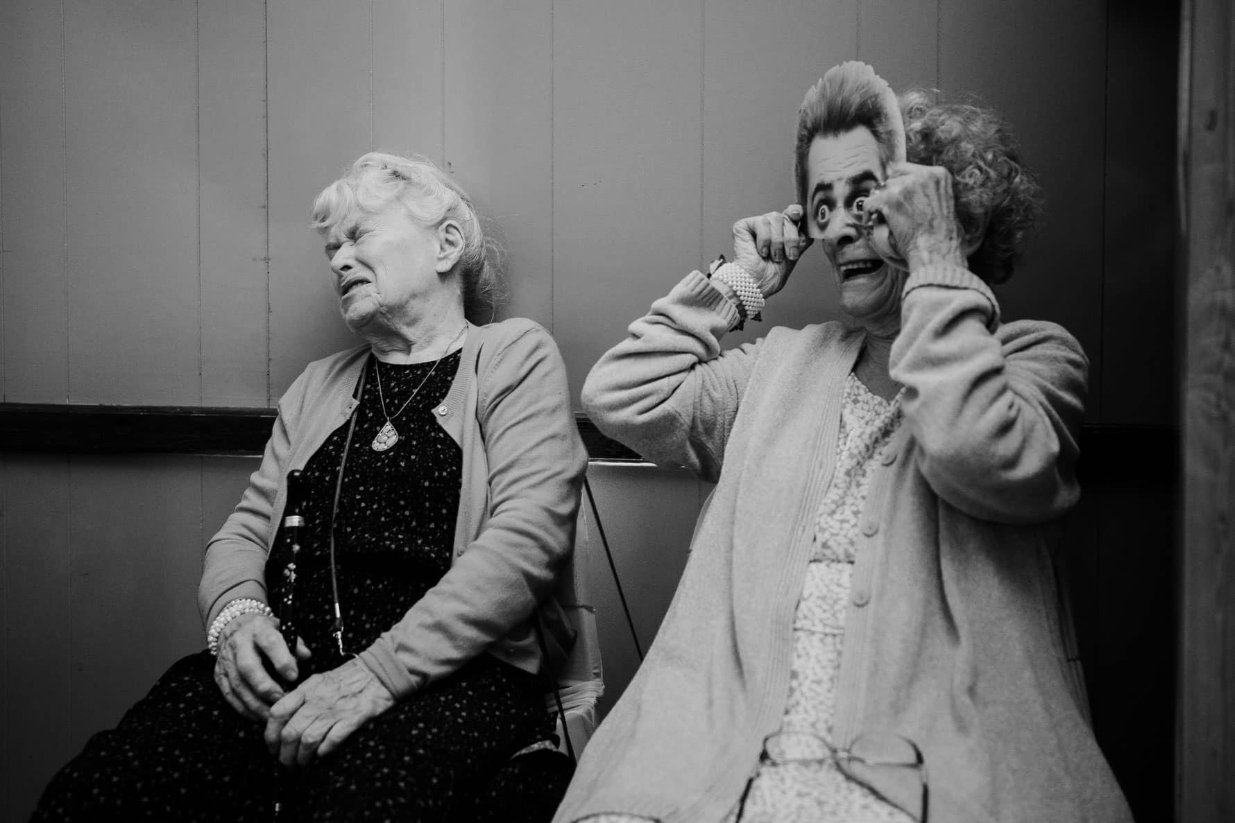 two ladies at a wedding reception, one wearing a mask to make the other one laugh