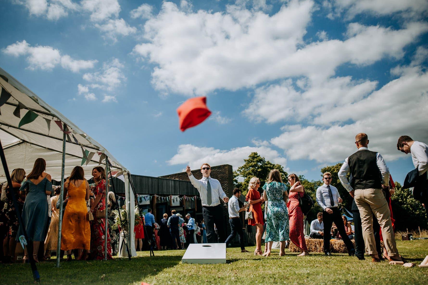 Man throwing a beanbag at a wedding reception