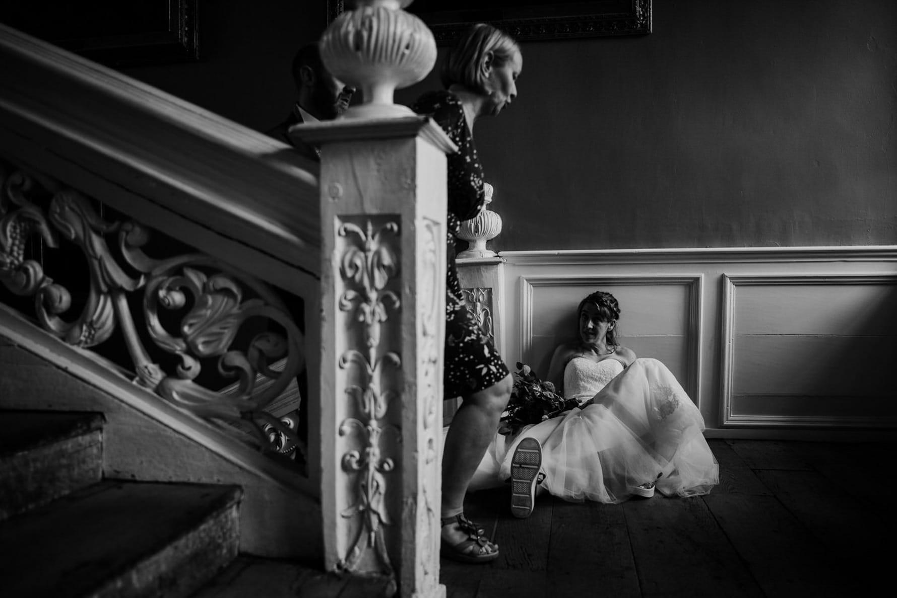 Bride sitting down to rest as a guest walks past
