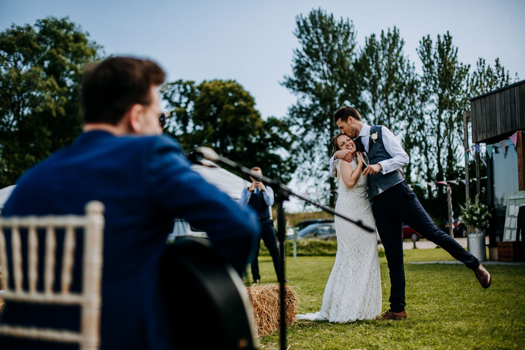 Bride and groom laughing in front of a band