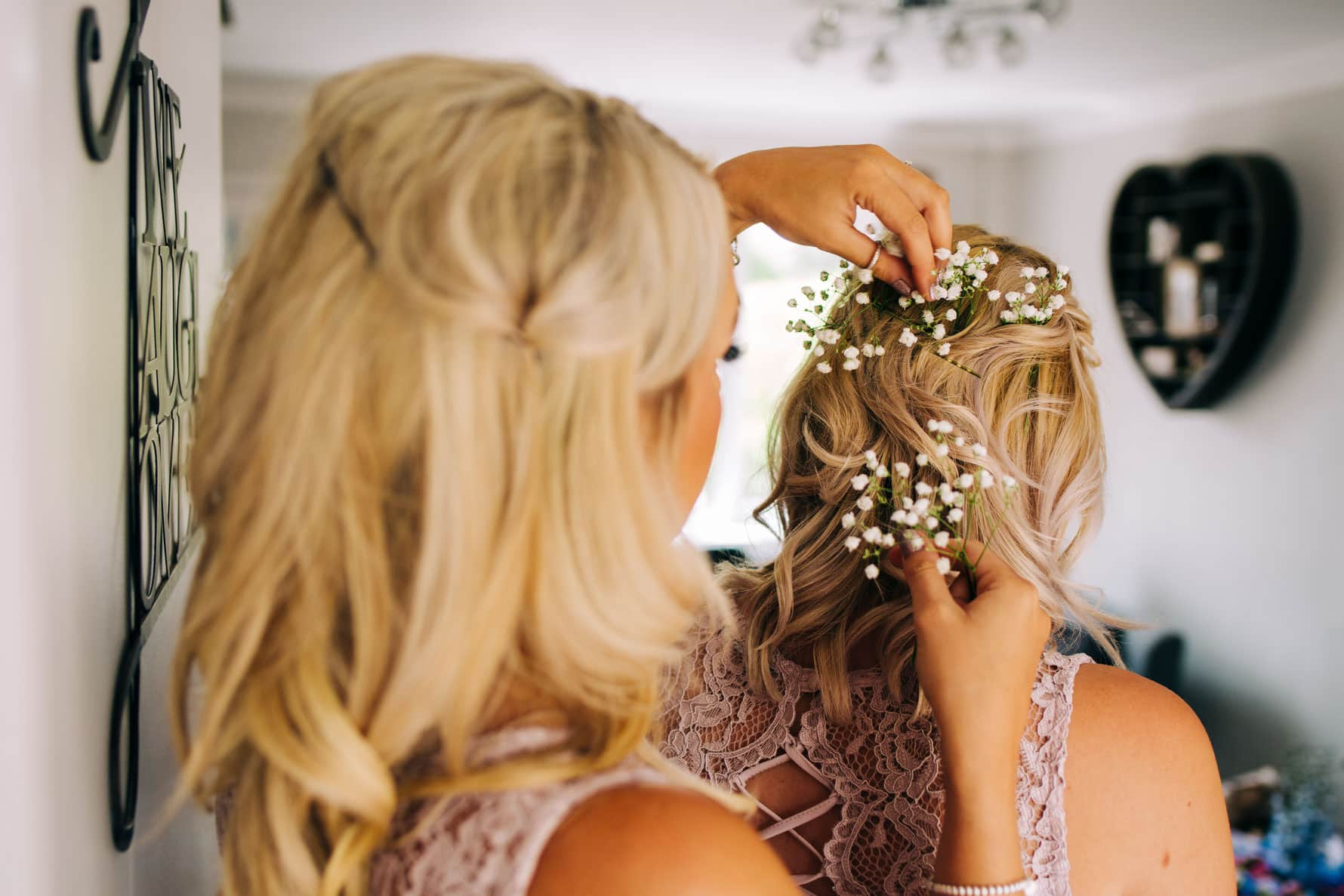 Bridesmaid putting flowers into another bridesmaids hair