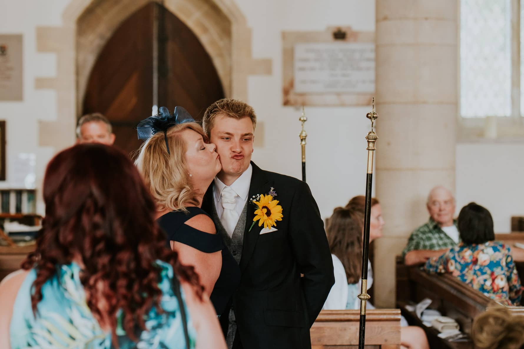 Groom getting a kiss from a guest