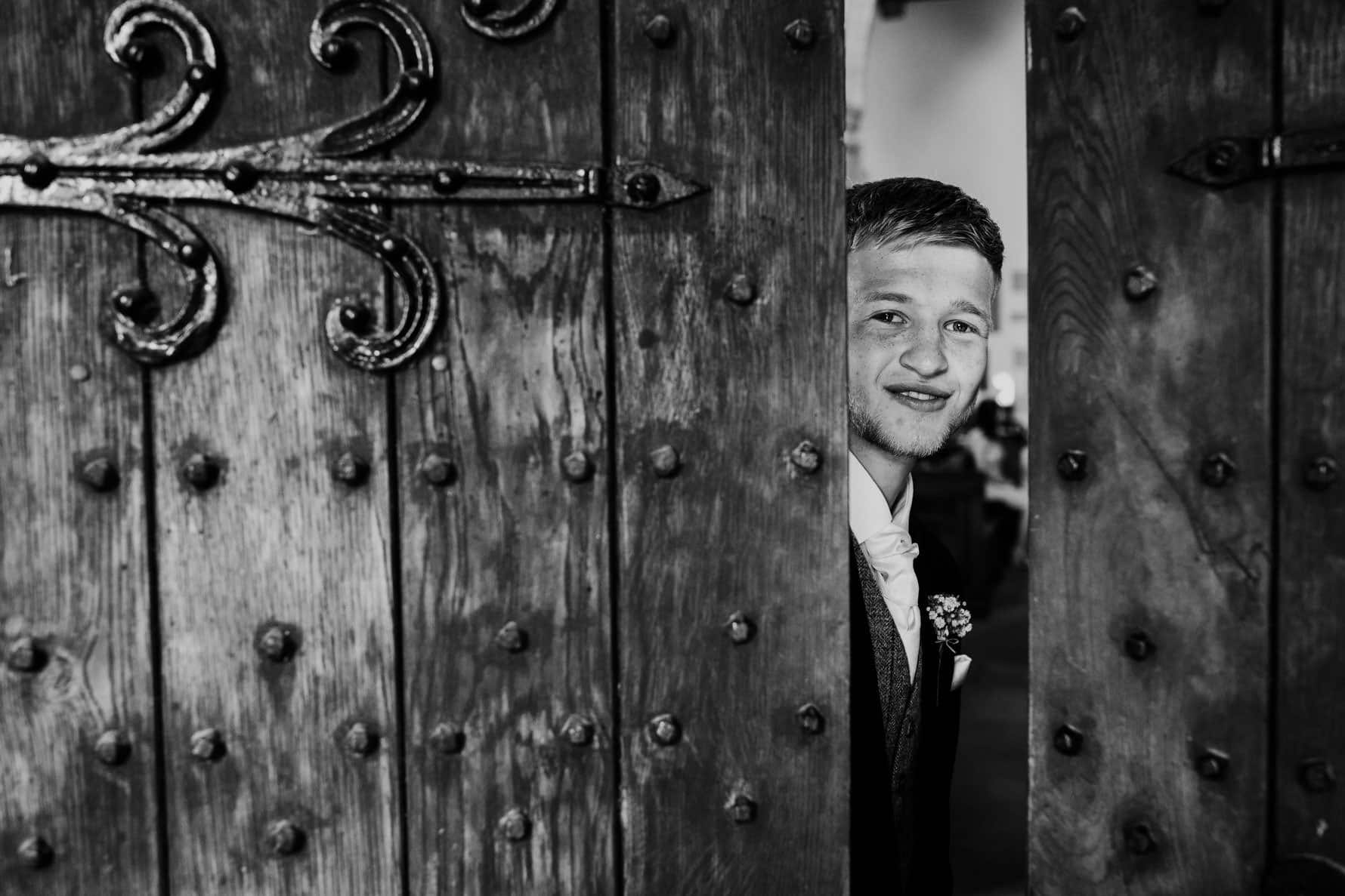 Groomsmen looking through the crack of a door