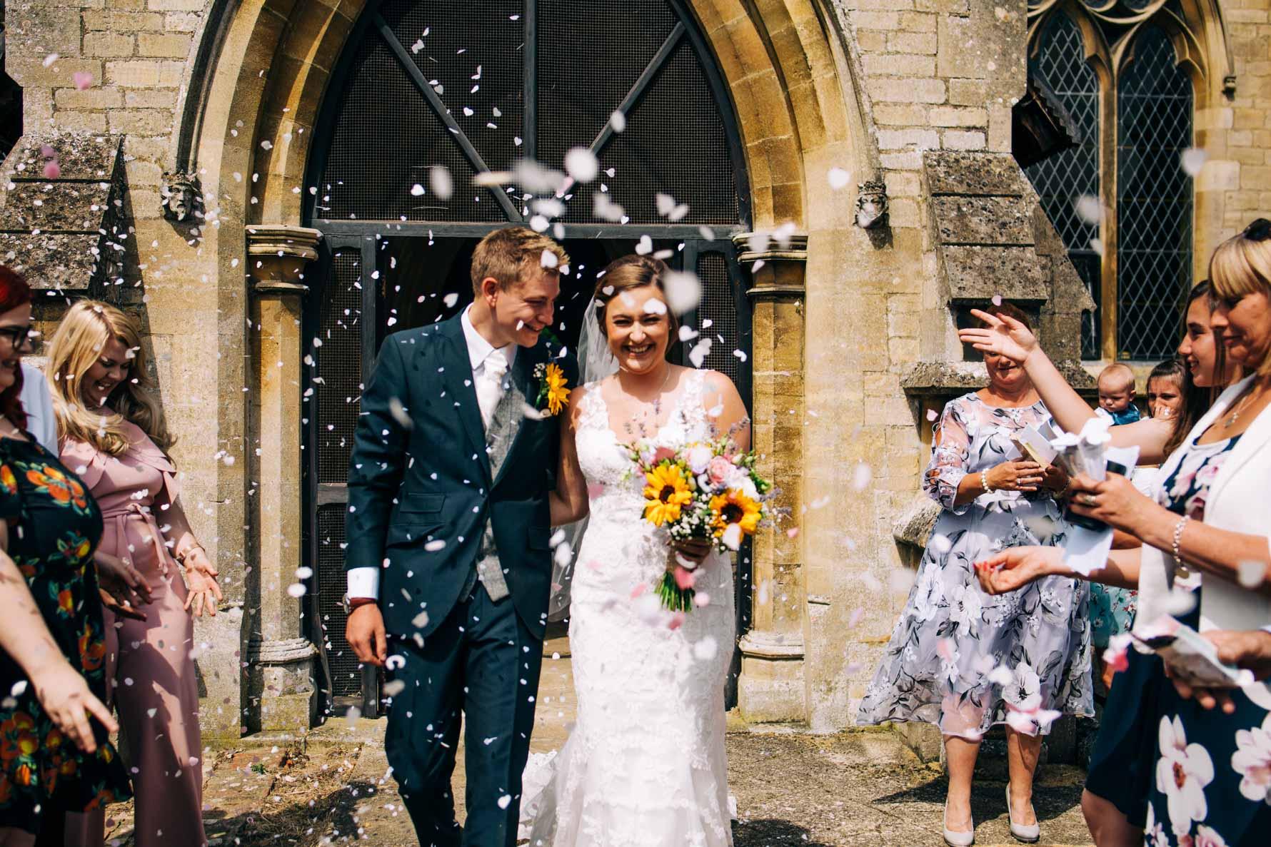 Bride and groom walking through confetti - Exton Park wedding photographer