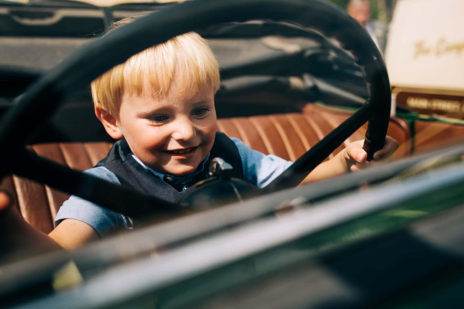 A boy pretending to drive a car