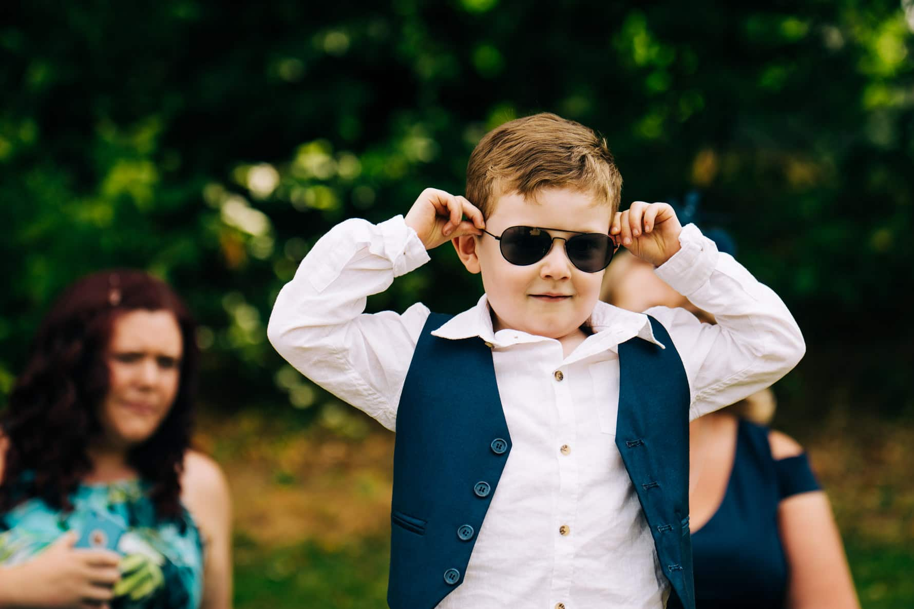 A kid at a wedding wearing sunglasses looking cool