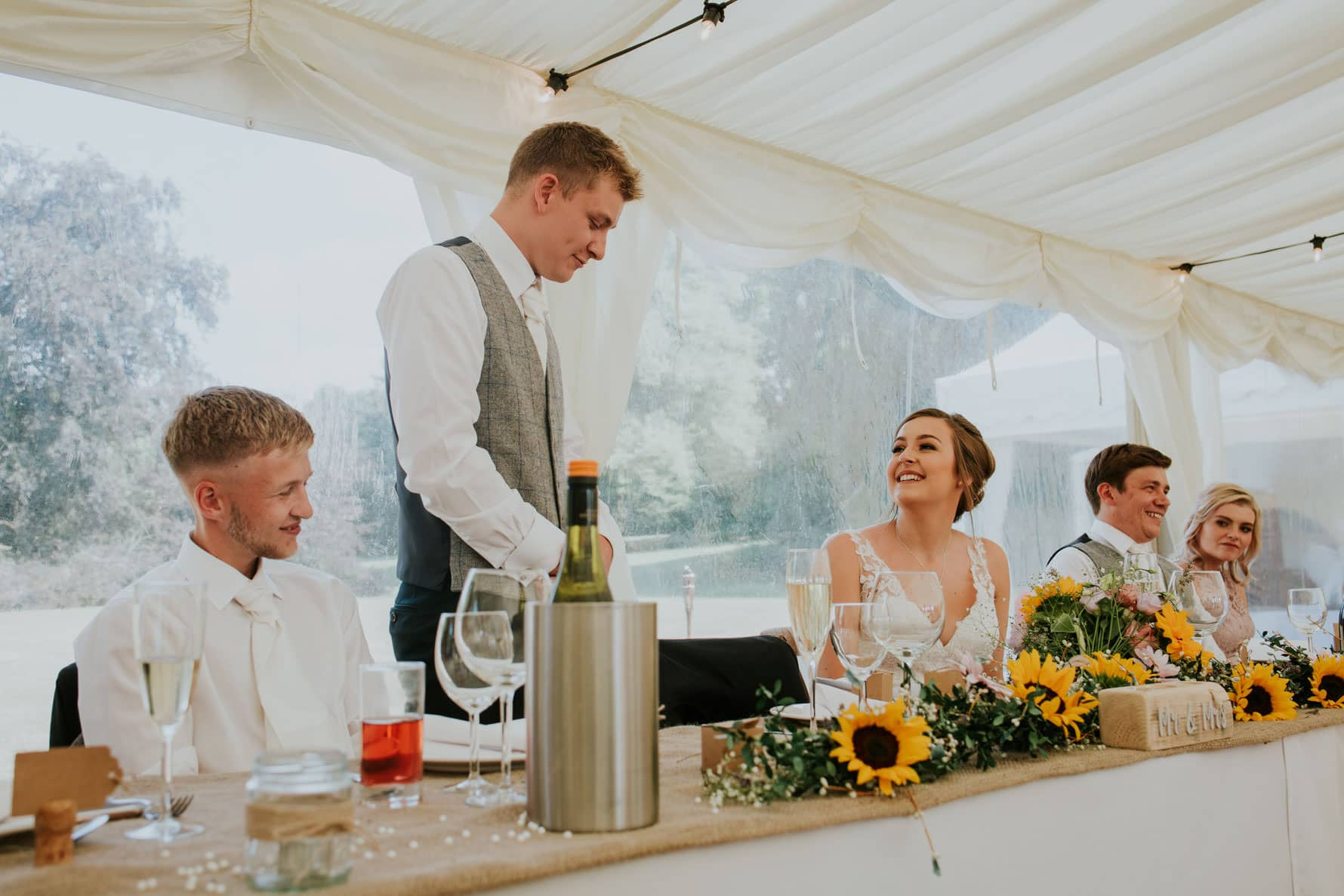 Top table during wedding speeches, bride looking at the groom