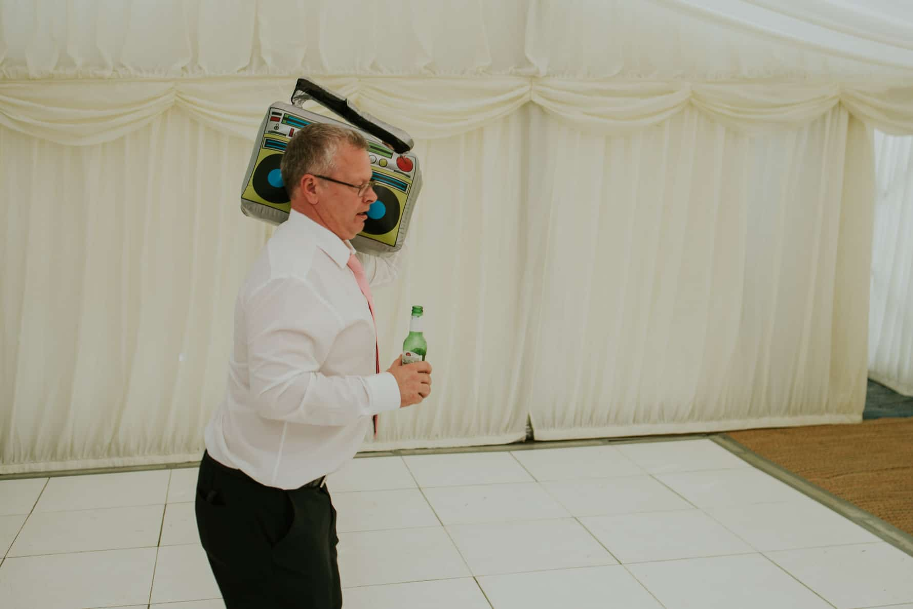 Man dancing with an inflatable stereo at a wedding
