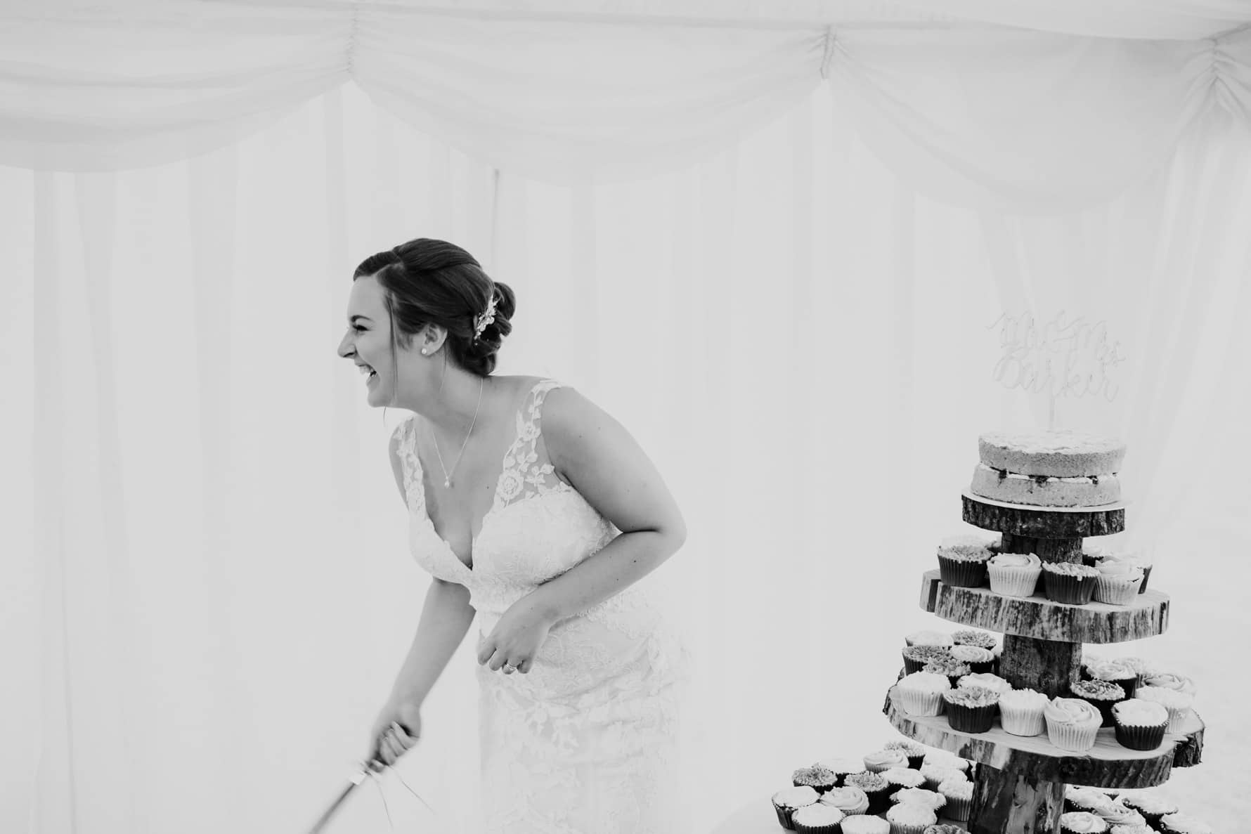 A bride just before she cuts her wedding cake - laughing
