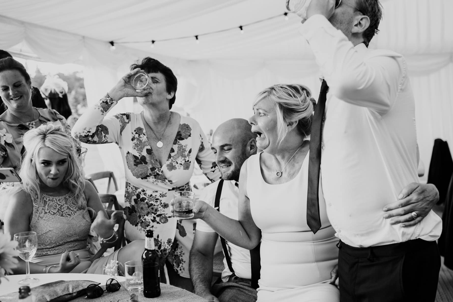 Group of wedding guests drinking shots