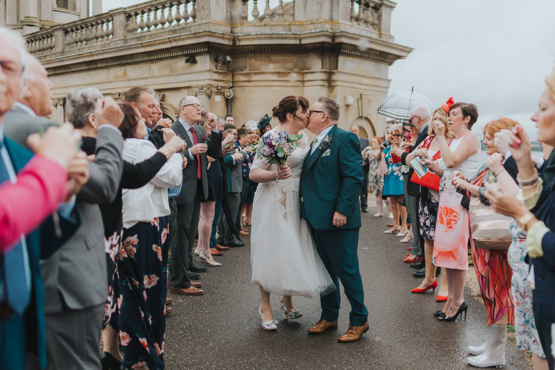 Bride and groom stood outside Normanton church surrounded by guests