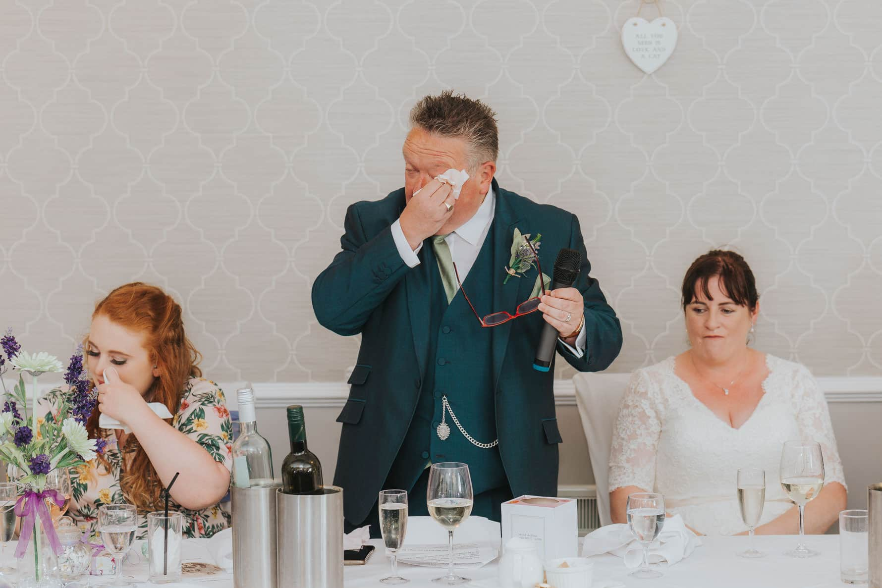 A groom drying his tears while making a speech