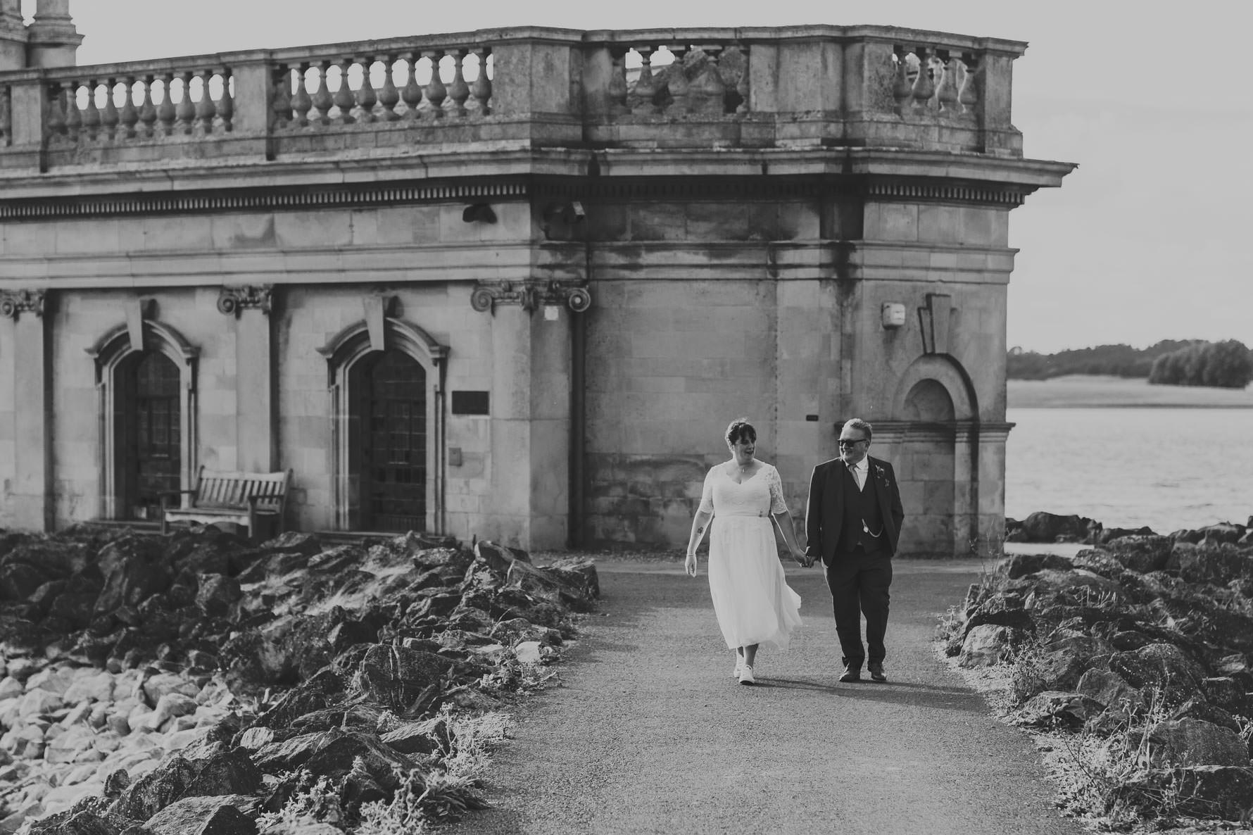 Bride and groom walking in front of Normanton church