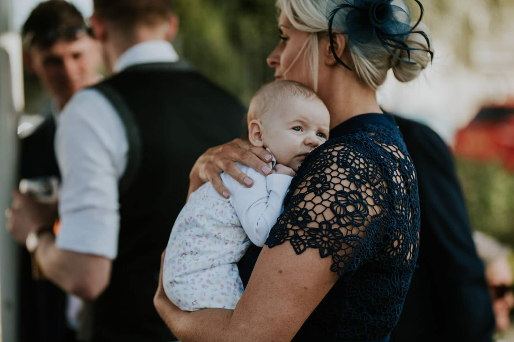 small baby being held by a wedding guest