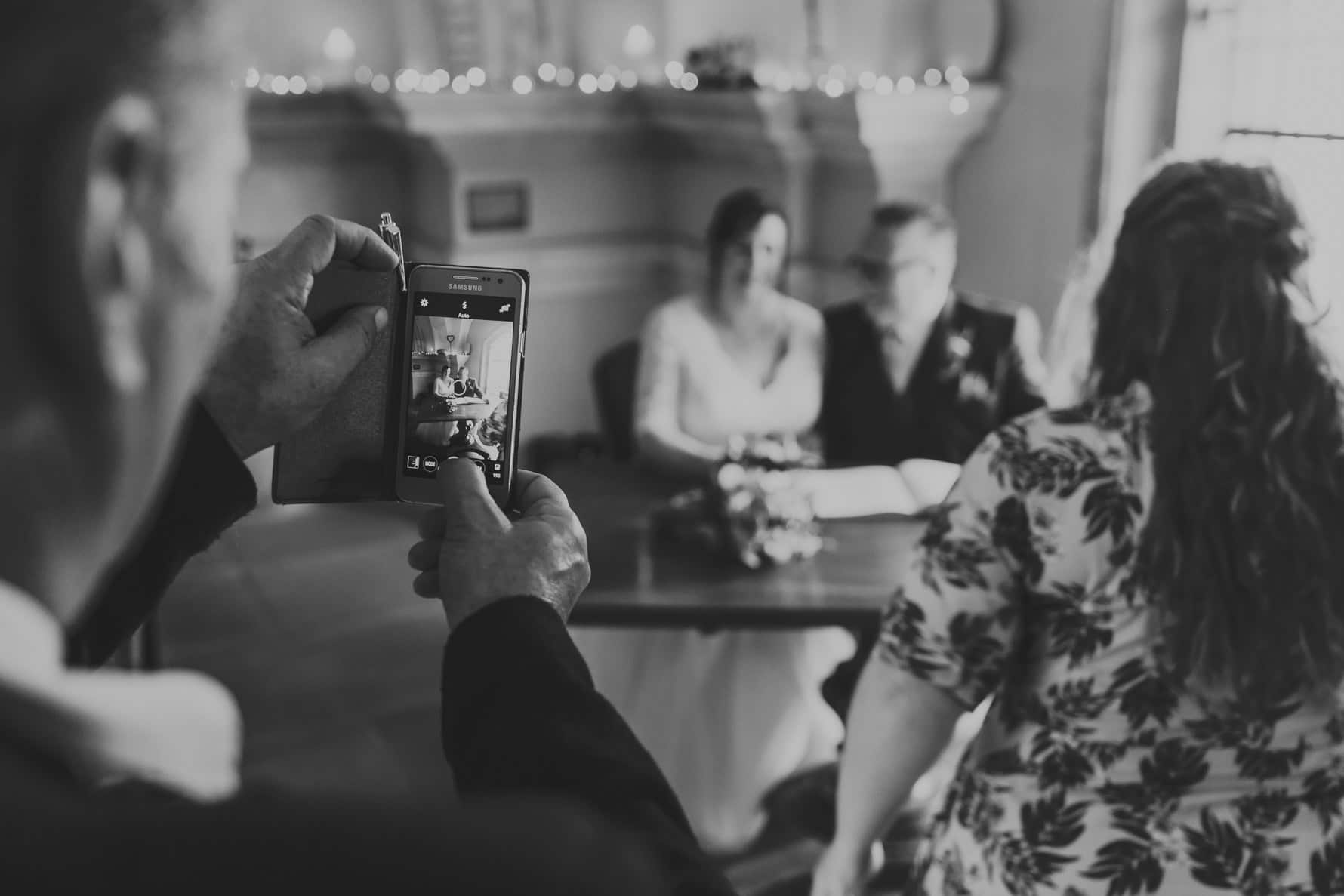 Wedding guest taking a picture of the bride and groom signing the register